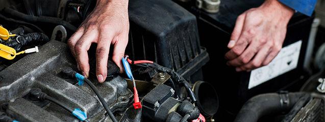 un garagiste fait des réparations sur un moteur mazda